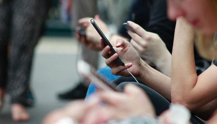 Personer tittar ned i smartphones